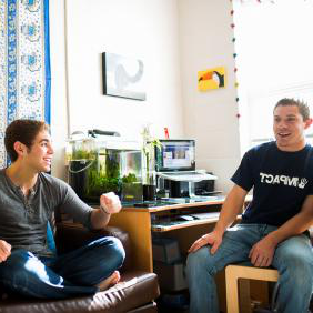 Two male students in dorm room talking and laughing.